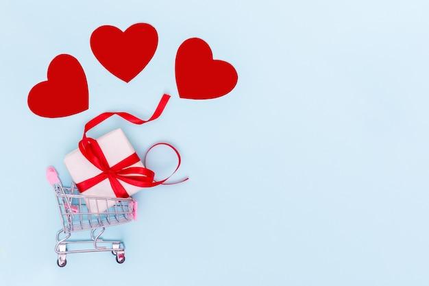발렌타인 데이 판매 개념. 빨간 리본과 빨간 사랑의 마음을위한 선물 상자가있는 쇼핑 트롤리