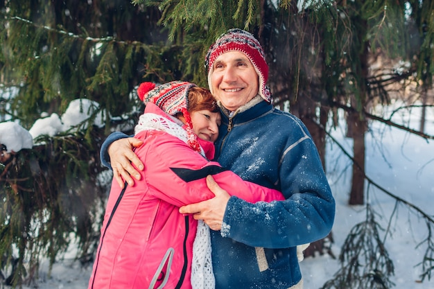 Valentine's day. senior family couple hugging in winter forest. happy man and woman walking outdoors.