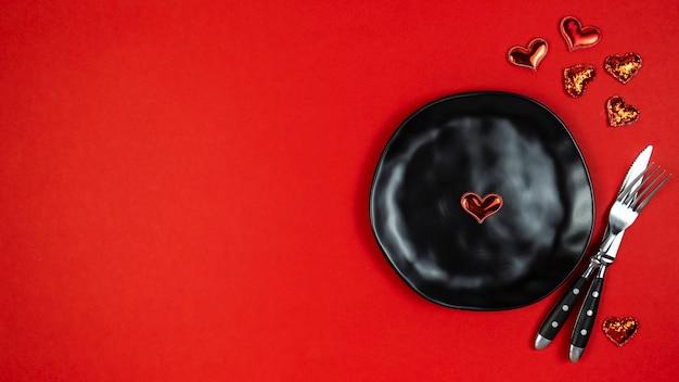 赤い背景にフォーク、ナイフ、プレート、ハートのバレンタインデーの設定。上面図、テキストスペース