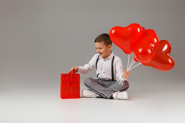 발렌타인 데이. 붉은 심장 모양의 풍선과 선물 종이 봉지를 들고 웃는 세련된 아이 소년