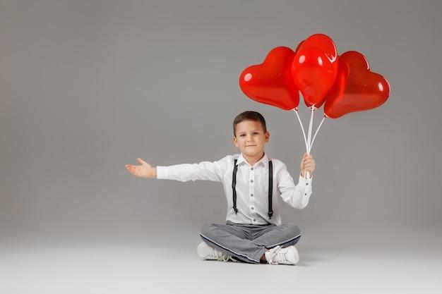 발렌타인 데이. 붉은 심장 모양의 풍선을 들고 바닥에 앉아 웃는 세련된 아이 소년