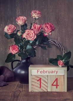 Valentine's day still life with wooden calendar, pink roses and hearts on dark