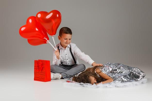 발렌타인 데이. 세련 된 아이 소년 붉은 심장 모양의 풍선을 보유 하 고 실버 드레스에 화가 어린 소녀 근처 거짓말