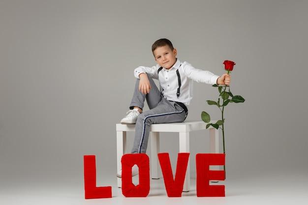 День святого валентина. стильный ребенок мальчик с красной розой сидит возле красных букв слова любовь на сером фоне студии