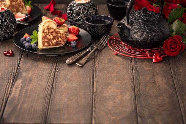 Valentine's day surface with delicious pancakes in form of heart, green tea, black teapot, candles and roses. valentines day concept greeting card. copy space