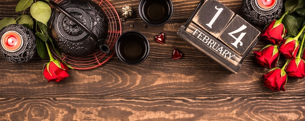 Valentine's day surface with green tea, black teapot, candles, roses and wooden calendar. valentines day concept. top view. banner, copy space