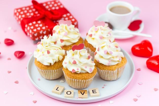 バレンタインデーのお菓子。ハート、ギフトボックス、コーヒーを飾ったカップケーキ