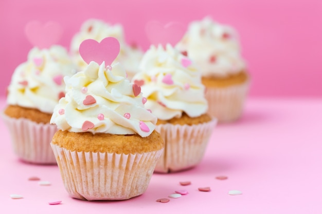 Valentine's day sweets. cupcakes decorated hearts on a pink background