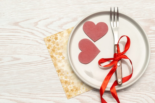 Сервировка tabble дня святого валентина со столовыми приборами и салфеткой на белом фоне романтический ужин знакомств концепция с копией пространства.