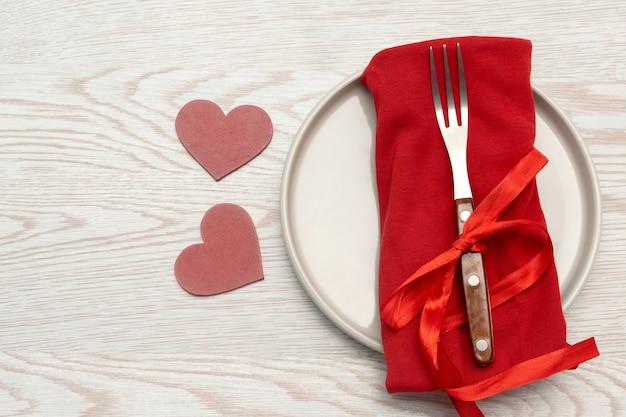Сервировка tabble дня святого валентина со столовыми приборами и красной салфеткой на белом фоне романтический ужин концепция с копией пространства.