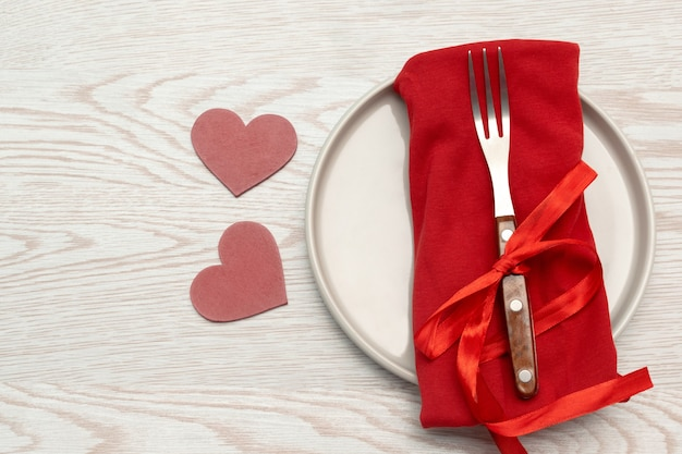 Valentine's day tabble serving with cutlery and red napkin on white background romantic dinner concept with copy space.