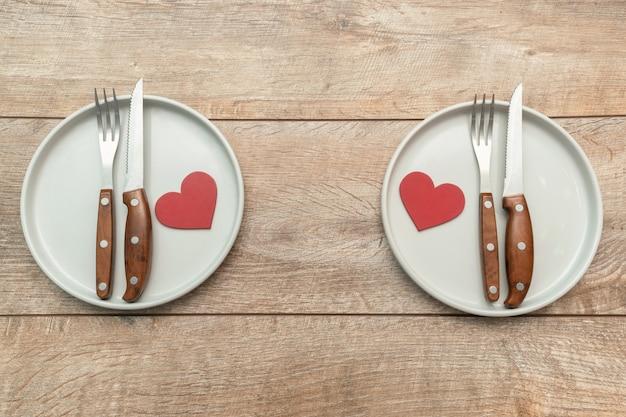 Сервировка табла ко дню святого валентина с тарелками и столовым серебром на деревенском деревянном фоне концепция романтического ужина и свиданий