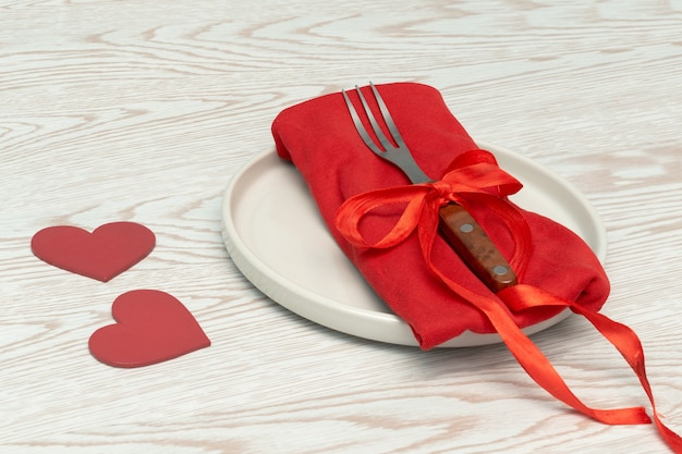 Сервировка стола ко дню святого валентина со столовыми приборами и красной салфеткой, концепция романтического ужина с декором в виде сердца