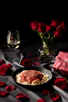 Valentine's day table set with pasta and bouquet of roses