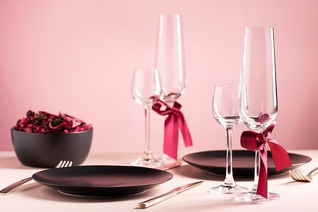 Сервировка стола ко дню святого валентина на двоих с засушенными цветами на розовом фоне