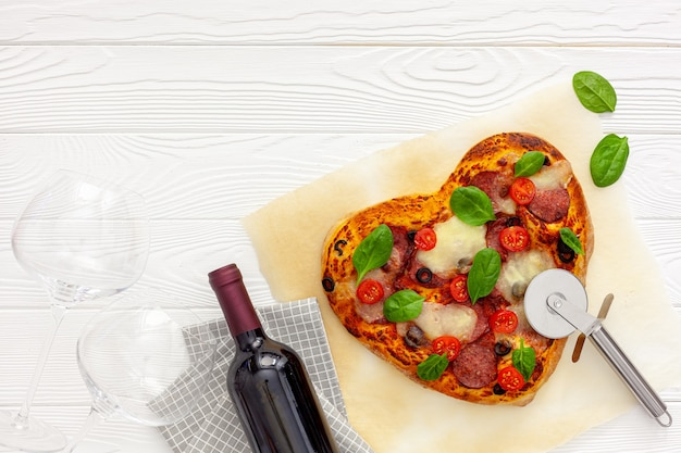 Valentine's day table setting. heart pizza with wine