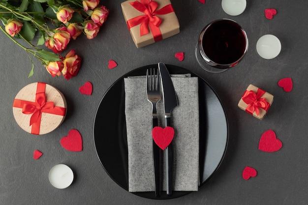 バレンタインデーのテーブルセッティング、黒い表面に食器、ギフト、ワイン、花、フラットレイ