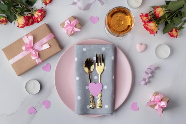 大理石の表面に食器、バラ、ギフト、キャンドルを置いたバレンタインデーのテーブルセッティング、フラットレイ