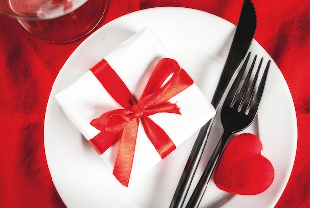 Valentine's day table setting with plate, fork, knife, gift box and red heart, on red tablecloth scene top view