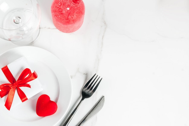 Valentine's day table setting with plate, gift box and red heart, on white marble scene top view