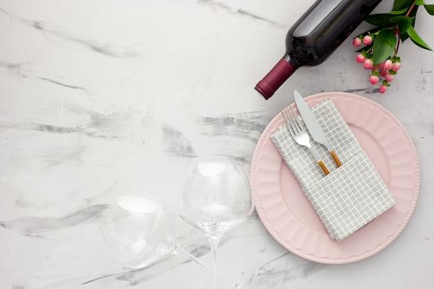 Сервировка стола на день святого валентина с тарелкой, вином и бокалами