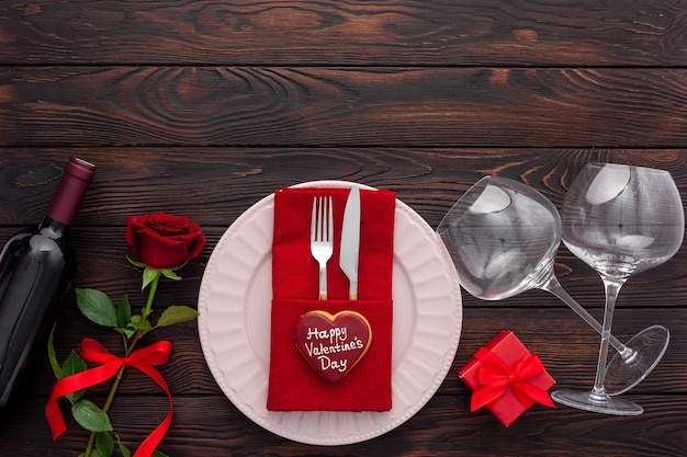 Valentine's day table setting with plate, wine and glasses