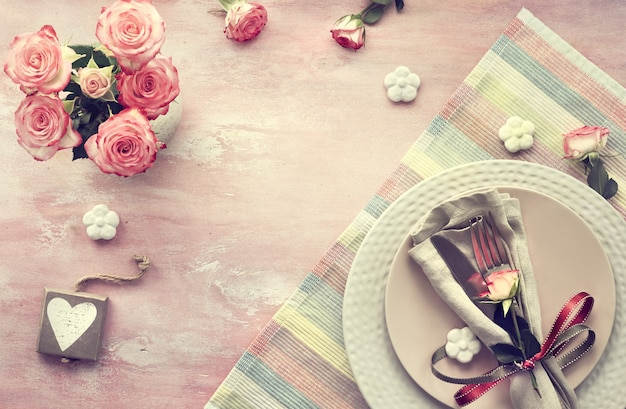 Valentine's day table setup, top view on  light pink background. wooden calendar, napkin and crockery, decorated with rose bud and ribbons, ceramic flowers and pink roses.