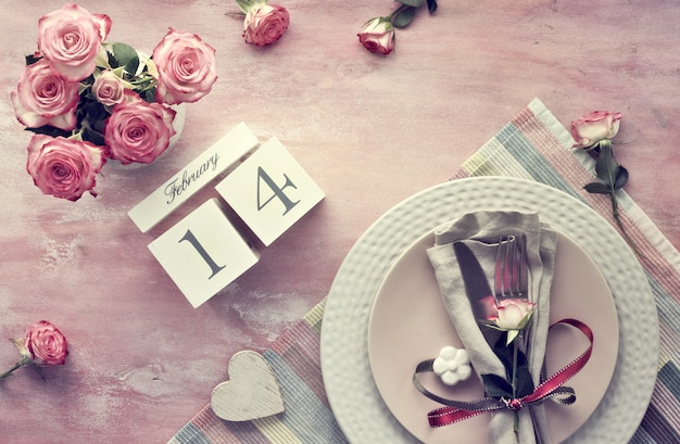 Valentine's day table setup, top view on  light pink wall. wooden calendar, napkin and crockery, decorated with rose bud and ribbons, ceramic flowers and pink roses.