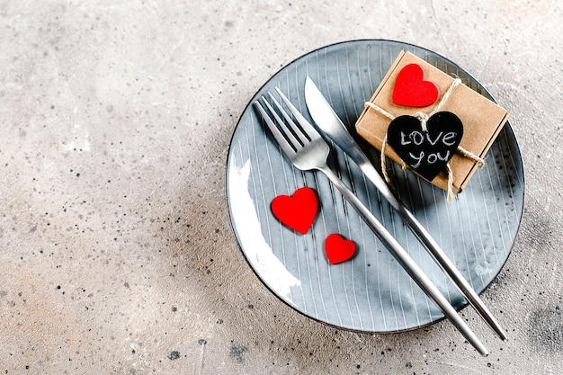 Valentine's day table with gift box, cutlery, and red hearts on a plate on light marble background