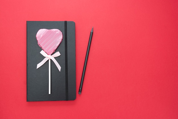 Valentine's day template. black notebook on red background with a heart shaped lollipop and copy space.