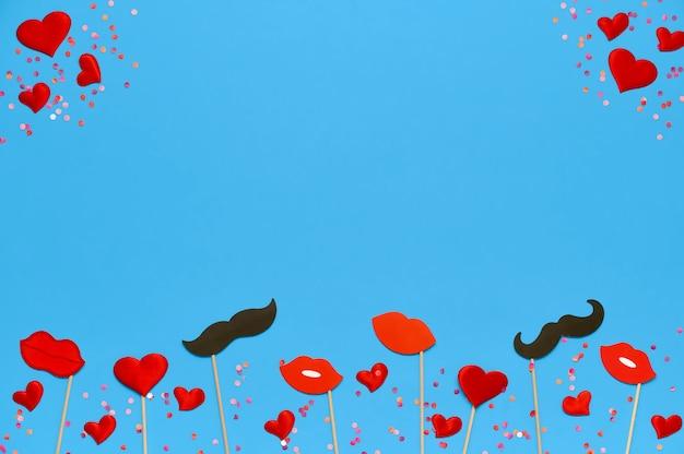 Шаблон дня святого валентина с праздничными аксессуарами, губами, сердцами и декором усов на синем с копией пространства. вид сверху, плоская планировка