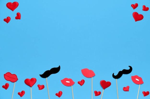 Шаблон дня святого валентина с праздничными аксессуарами, губами, сердечками и декором усов на синем.