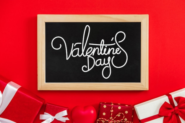 Valentine's day text with gift boxes on red background