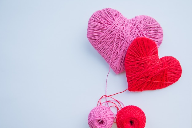 Valentine's day themed still life with love hearts. together forever. colorful yarn balls isolated.