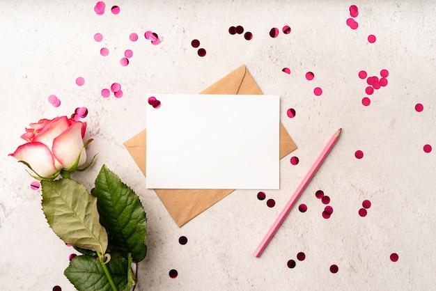 발렌타인 데이. 빈 편지와 봉투 핑크 연필, 색종이와 장미의 상위 뷰