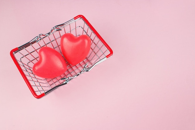 Valentine's day, top view two red hearts on toy basket on pink background, copy space, love concept