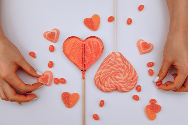 Valentine's day.  view from above.  the girl's hands shift candies in the form of hearts on a white background