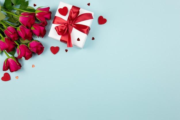 발렌타인 데이, 결혼식 또는 어머니의 날 평면은 파스텔 블루에 빨간 리본, 장미와 하트 선물 상자와 함께 누워 있습니다.