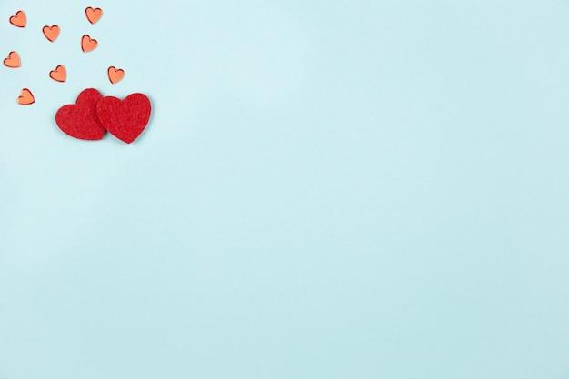 발렌타인 데이, 결혼식 또는 어머니의 날 평면 파스텔 블루에 빨간 하트와 함께 누워.