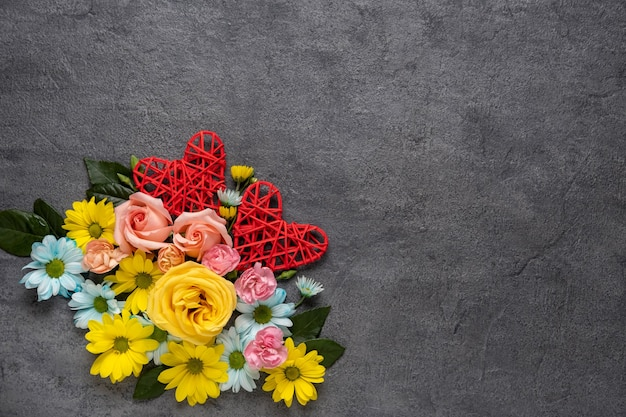Valentine's day or wedding romantic concept with flowers and red hearts on grey background. top view, copy space.
