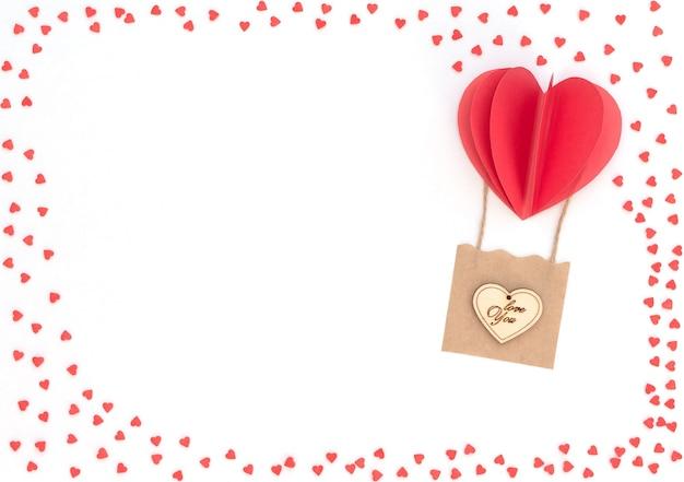 バレンタインデーの白い背景に赤いハートの風船、木製のハートとたくさんの赤いハートのバスケットが付いています。バレンタイングリーティングカード。コピースペースのあるフラットレイスタイル。愛と幸福の概念。