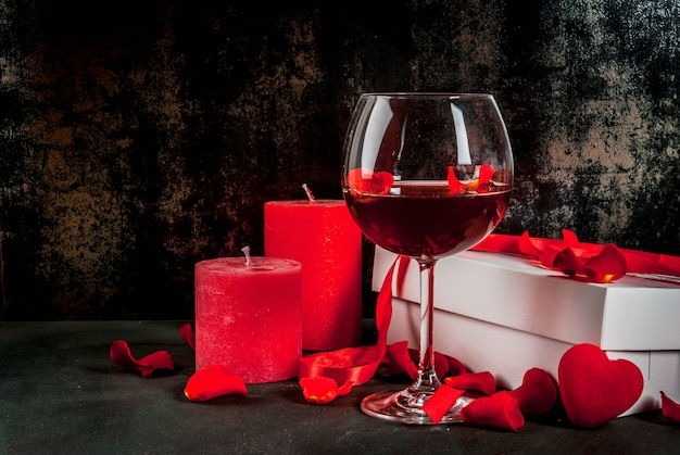 Valentine's day , white wrapped gift box with red ribbon, rose flower petals, red wine glass, with red candle, on dark stone , copyspace