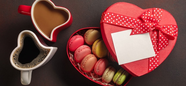 Valentine's day with gifts, a heart-shaped box, cups of coffee, heart-shaped cookies, macaroons and a blackboard. top view with copy space.