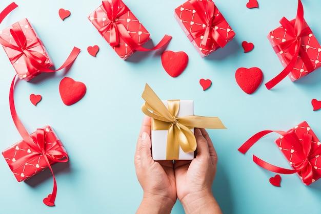 День святого валентина. женщина руки держит подарочную или подарочную коробку украшена