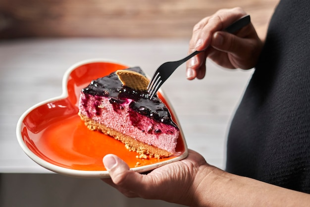A valentine's day. woman taking a slice of wild berry mouse cake from a heart shaped plate.