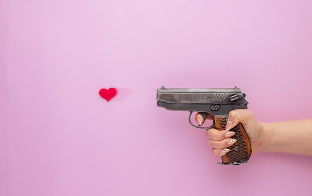 Valentine's day . womans hand holding a gun and shooting with heart on pink background.