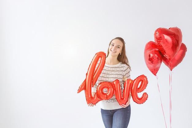 День святого валентина. слово любовные письма от надувных. девушка держит большое слово любовь и сердце шары