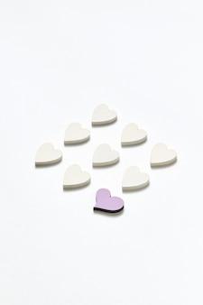 Декоративный диагональный узор валентинки из бумажных сердечек ручной работы белого цвета и одно из них розовое на светло-серой стене с мягкими тенями, копией пространства.