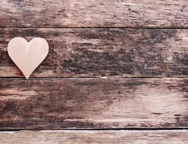 Сердце валентинки на выдержанном деревянном фоне. шероховатая текстура натуральных досок.