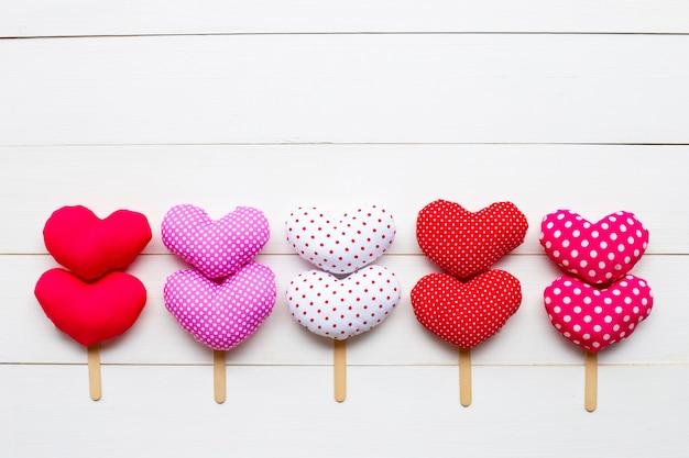 Valentine's hearts on white wooden background.